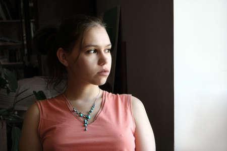 anguish: Unhappy teenage girl  by the window