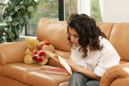Teenage girl reading a book on a couch Imagens - 274403