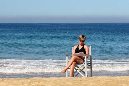 Woman reading on the beach Stock Photo