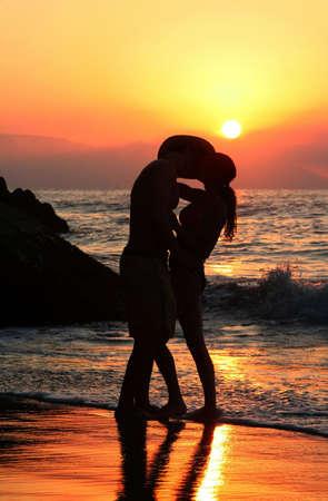 Couple on the beach at sunset Standard-Bild