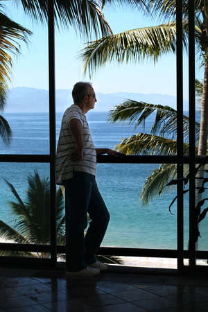 Man standing by the window in a tropical resort