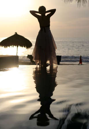 gentle dream vacation: Woman and her reflection in a pool by the ocean