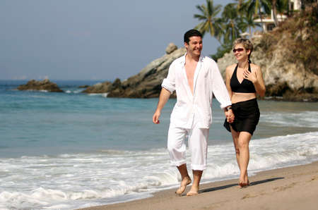 travelling: Young couple walking on the beach