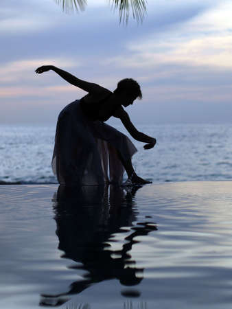 Woman and her reflection in a pool by the ocean photo