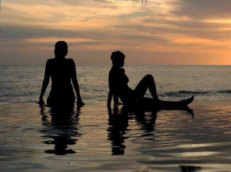 lesbienne: Les femmes et leurs r�flexions dans une piscine par l'oc�an