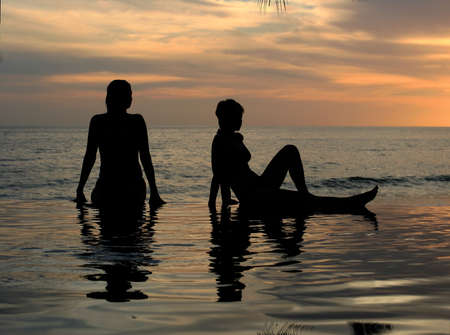 Women and their reflections in a pool by the ocean Stock Photo