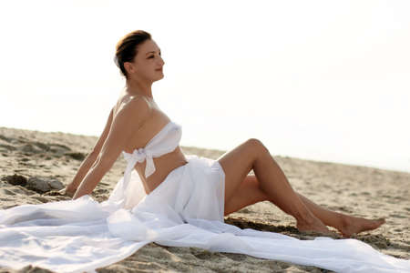 Woman in white clothes sitting on the beach Stock Photo
