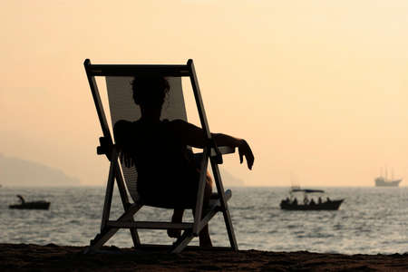 Woman sitting in the chair watching sunset at the beach Stock Photo - 291425