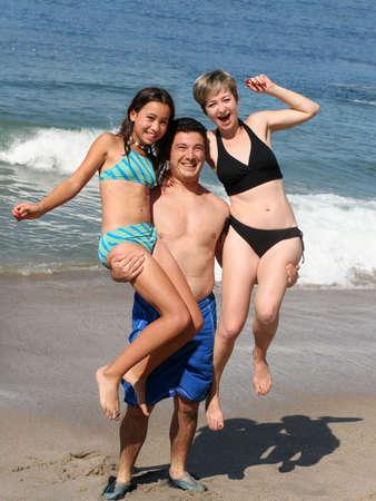 child bikini: A man holding his wife and teenage daughter Stock Photo