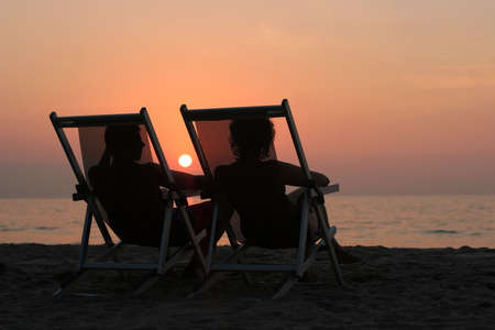 romance: Couple sitting in the chairs watching sunset at the beach
