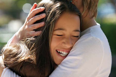 moment: Mother hugging her happy daughter Stock Photo