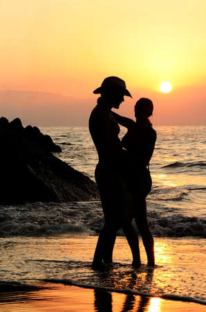 Couple on the beach at sunset Imagens