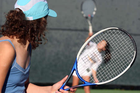 Two girls playing tennis photo