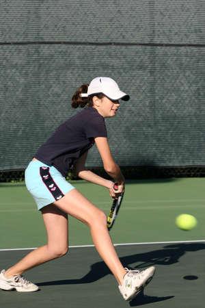 jugando tenis: Muchacha joven que juega a tenis