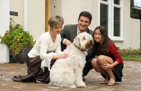 Happy family with a dog in front of the home photo