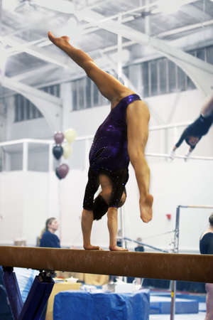 gymnastics sports: Gymnast competing on beam Stock Photo