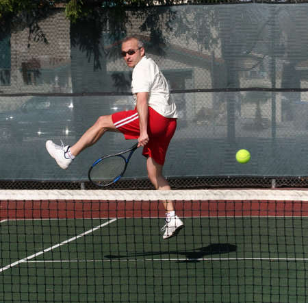 Middleage man playing tennis photo