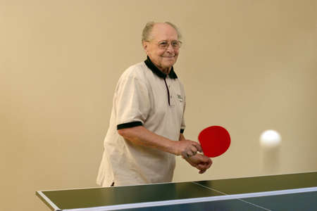 Grandfather playing ping pong Stock Photo