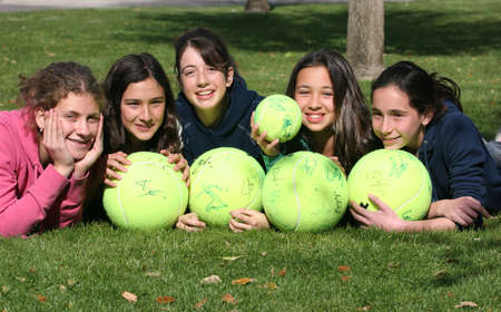 Happy girls with big tennis balls photo