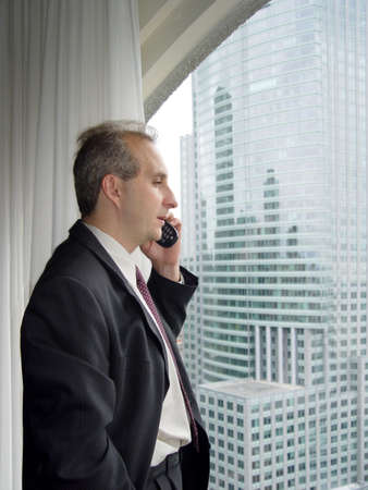 deal making: Businessman talking on the phone by the window Stock Photo