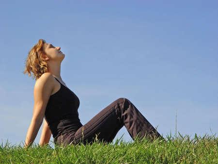 Beautiful woman sitting in the grass Stock Photo