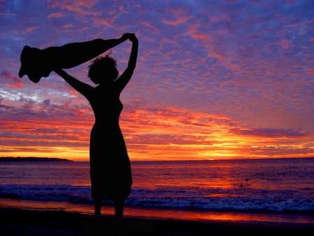 scarf beach: Mujer en la playa al atardecer  Foto de archivo
