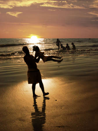 Father playing with his daughter on the beach at sunset