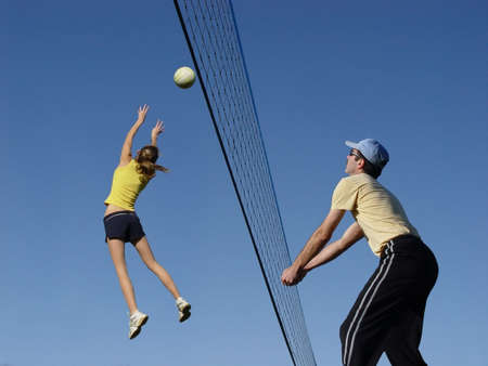 Men and a girl playing volleyball photo