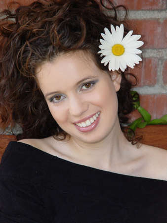 A beautiful girl laughing against brick wall with a big daisy in her hair Stock Photo - 347475