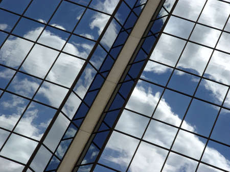Blue sky and clouds reflected in the glass building in downtown Toronto