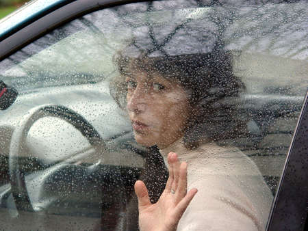 A woman in a car behind the wheel. Window covered with rain drops. photo