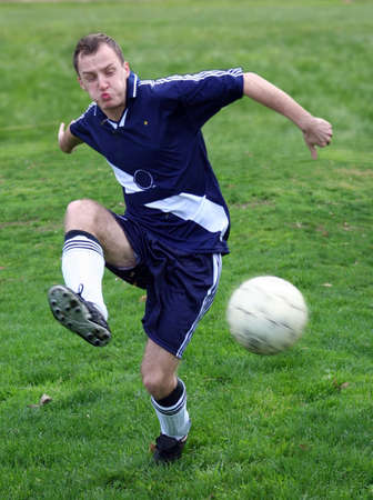 Soccer player hitting a ball photo
