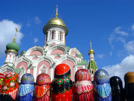 Row of Matryoshkas (Russian nesting doll) and a church at Red Square Stock Photo