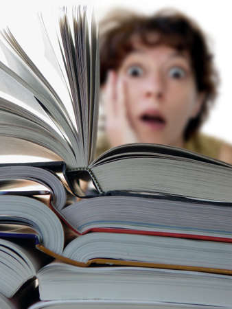 Terrified woman behind a big pile of books