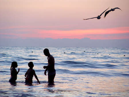 Family playing in the water at sunset Stock Photo