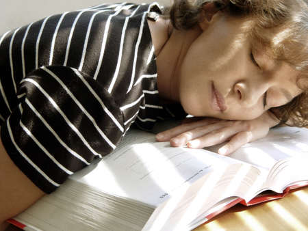 Tired girl is sleeping on her book Stock Photo - 347270