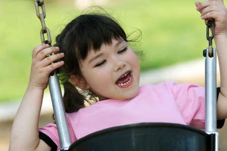 Cute little girl swinging photo