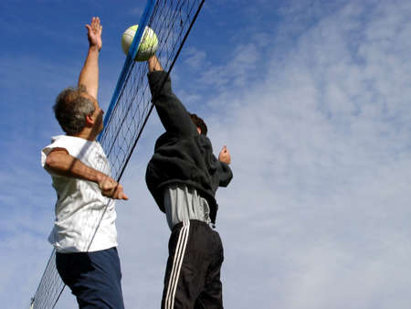 Young men hitting the ball over the net photo