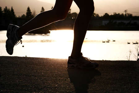 Woman jogging along a river at sunset Stock Photo - 364542