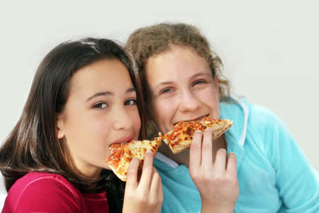 Two girls eating pizza photo