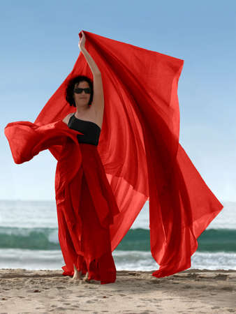 Woman on the beach with a red scarf photo
