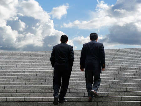 Two business men walking up the stairs