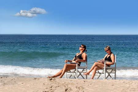 2 women reading on the beach photo