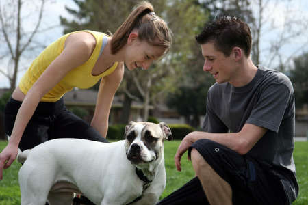 smooch: Teenagers playing with a dog in the park Stock Photo