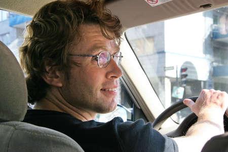 hombre conduciendo: Hombre joven que conduce en una ciudad