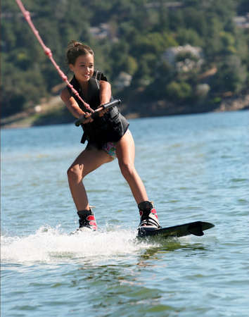 Girl wakeboarding on the lake photo
