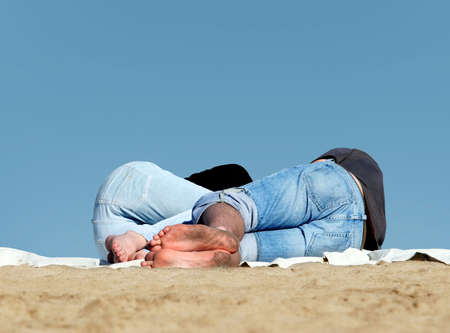 Couple sleeping on the beach with blue sky as a background photo
