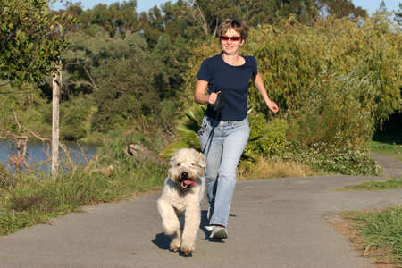 Woman running with her dog in the park photo