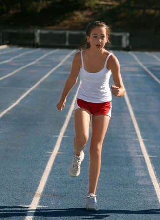 Girl exercising on a blue racetrack photo