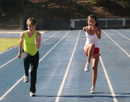Mother and daughter exercising on a blue racetrack Stock Photo